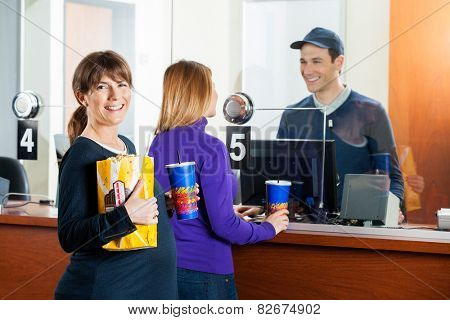 Portrait of happy woman holding snacks while friend buying movie tickets from male seller at box office