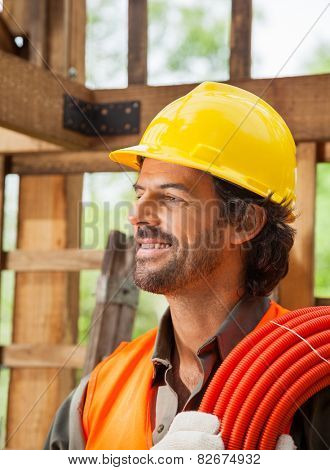 Smiling male worker with pipe at construction site