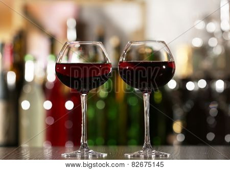 Two glasses of wine with bar on background
