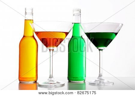 Colorful alcoholic beverages in glassware isolated on white