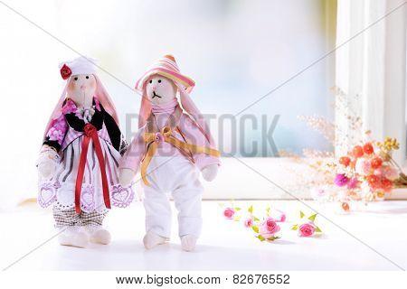 Handmade dolls near window close-up