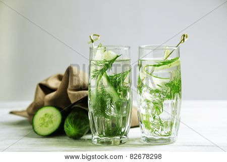 Glasses with fresh organic cucumber water on wooden table, on grey background