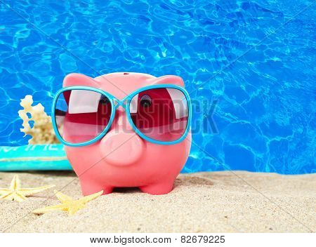 Piggy bank on beach background