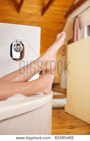 Bathtime. Girl's feet sticking out from bath tub.
