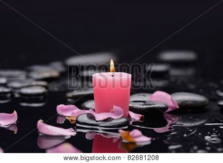 Beautiful red rose petals with candle and therapy stones
