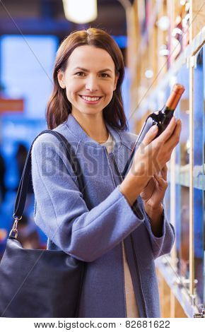 sale, shopping, consumerism and people concept - happy young woman choosing and buying wine in market