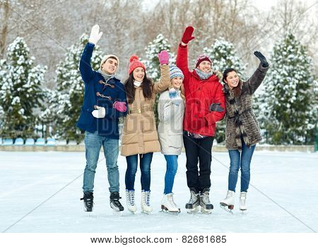 people, winter, friendship, sport and leisure concept - happy friends ice skating and waving hands on rink outdoors