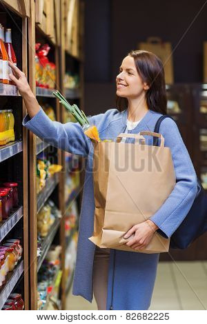 sale, shopping, consumerism and people concept - happy young woman with paper bag choosing and buying food in market