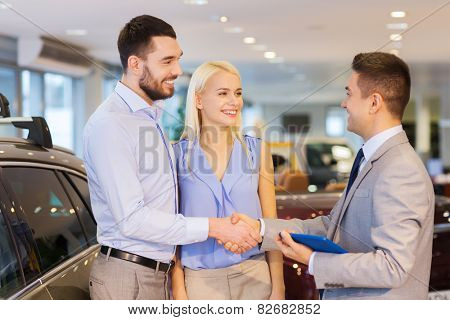 auto business, car sale, technology, gesture and people concept - happy couple with car dealer shaking hands in auto show or salon