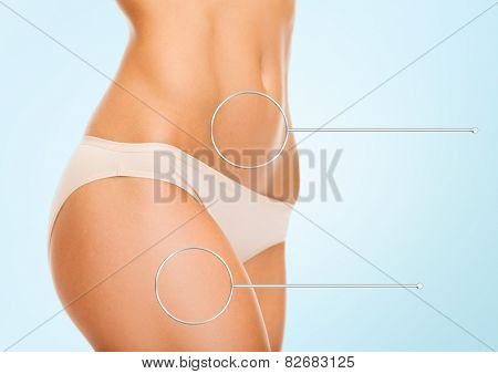 health, people and beauty concept - close up of woman hips and torso with magnifier over blue background