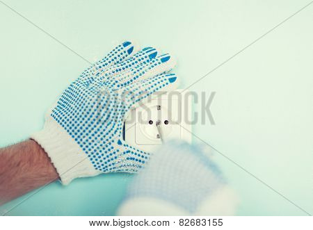 repair, building, electricity and home concept - close up of male in gloves installing new socket