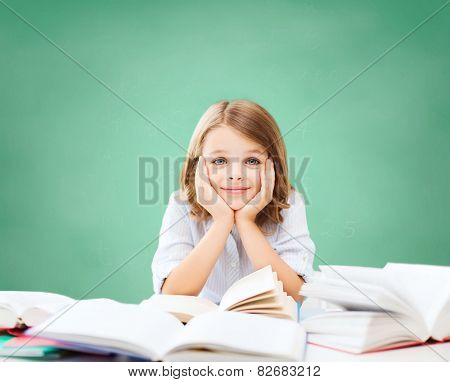 education, people, children and school concept - little student girl sitting at table with books over green chalk board background