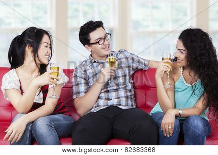 Friends Drinking Champagne On Sofa