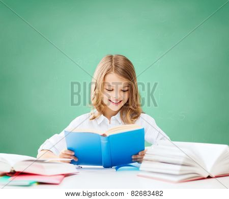 education, people, children and school concept - happy student girl reading book at school over green chalk board background
