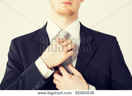 close up of man adjusting his tie.
