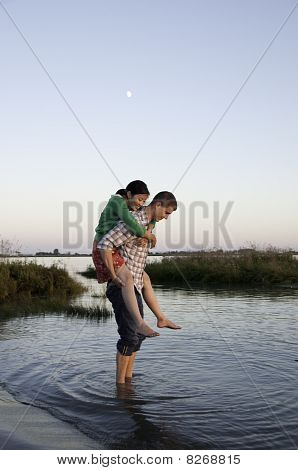 Girl On Boys Back Standing In  Water