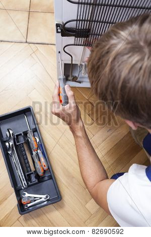 Man With Tools Repair The Fridge