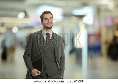 Young Businessman holding a tablet at the airport smiling