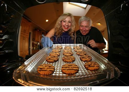 A nice lady bakes Cookies for her favorite window washer as a special Thank You. Shot from inside the oven out for a unique view. Focus on the cookie with the people slightly out of focus.