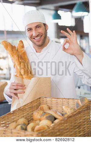 Baker showing basket of bread in the kitchen of the bakery