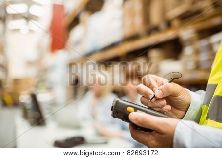 Close up of manager wearing yellow vest using handheld in a large warehouse