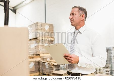 Warehouse manager checking his list on clipboard in a large warehouse