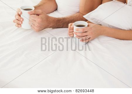 Mid section of young couple having coffee in bed at home in bedroom