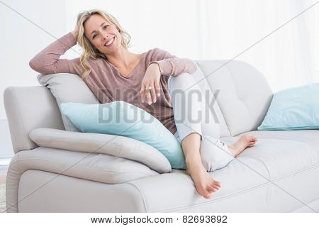 Pretty blonde relaxing and sitting on couch at home in the living room