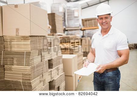 Smiling warehouse worker with clipboard in warehouse