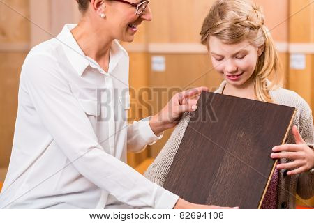 Family choosing parquet wood floor in home improvement store