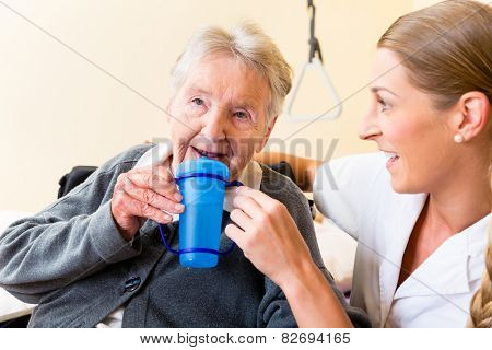 Nurse in nursing home giving drink to elderly woman sitting in wheelchair