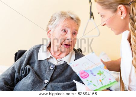Nurse giving birthday card to senior woman in nursing home sitting in wheelchair