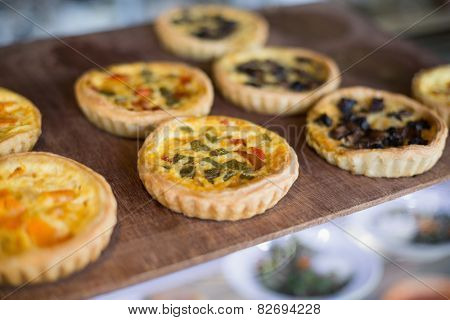 Delicious mini quiches on tray in the delicatessen
