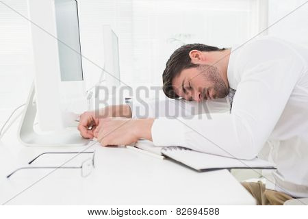 Tired businessman sleeping on keyboard in his office
