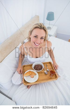 Happy blonde having breakfast in bed at hone in the bedroom