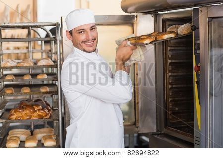 Happy baker taking out fresh bagels in the kitchen of the bakery