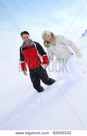 Couple walking in thick snow track