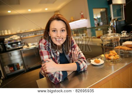 Cheerful waitress standing by shop counter