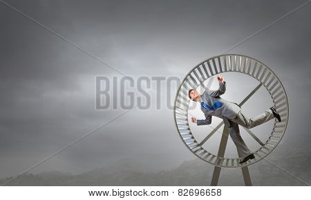 Young businessman running in huge hamster wheel