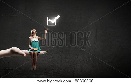 Young pretty girl sitting in palm with book