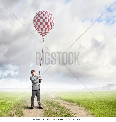 Young businessman holding colorful aerostat on lead