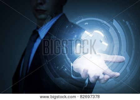 Close up of businessman holding puzzle element in palm