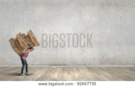 Young student girl lifting pile of old books on back