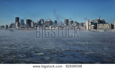 Montreal by a very cold day.  St-Lawrence river with steam on it with downtown Montreal in background in Quebec province in Canada