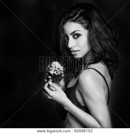 Beautiful exotic young woman seductively holding cup cake