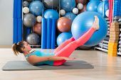 stock photo of pilates  - Ab exercise woman swiss ball leg lifts Pilates workout abs at gym - JPG