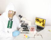 Постер, плакат: a research scientist wears a hazmat suit and gas mask as he works on a cure to the Zombie Apocalypse