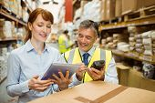 picture of warehouse  - Warehouse managers looking at tablet pc in a large warehouse - JPG