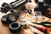 Building model cars. Radio control car assembly scene, RC car assembly on wooden work desk and tools poster