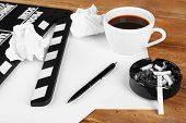 picture of butt  - Movie clapper with cup of coffee and ashtray with cigarette butts - JPG